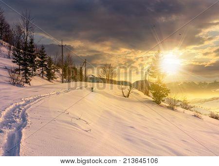 Rural Footpath Through Snowy Hillside At Sunset