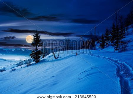 Rural Footpath Through Snowy Hillside At Night