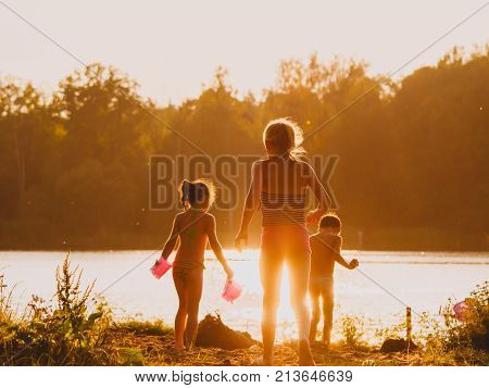 Three children play on the beach near the river in sunset light. Breeziness blessedness of childhood.