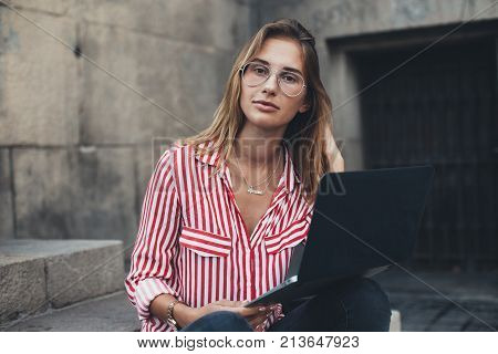 Portrait of casual fashionable and trendy dressed young millennial woman typing on keyboard or working remotely outdoors sitting on steps of office building or university concept young unconventional professional