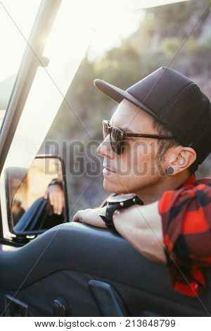 Portrait of driver middle aged man during road trip resting on window rest next to rear view mirror he weats tucker cap and trendy sunglasses warm sunset light concept freedom