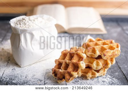 Belgian waffles and bag of flour - Baking theme image with tasty Belgian waffles surrounded by wheat flour and an open recipe book on a black wooden background.