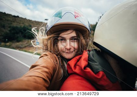 Beautiful young woman makes selfie while sits on passenger sit of motorcycle holds and hugs to driver boyfriend. Blonde hair blows in wind concept road trip and adventure