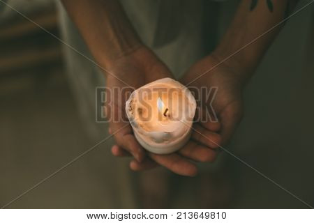 Tender and sensual woman hands hold small white wax candle slowly burning with tiny flame concept love and peace