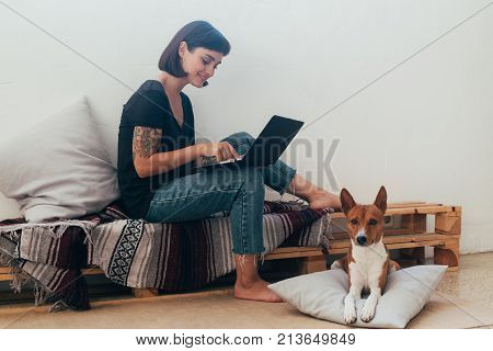 Pretty woman works from home or startup coworking space sits barefoot on bench and writes code or blog on laptop her best friend dog puppy lays next to her on pillow