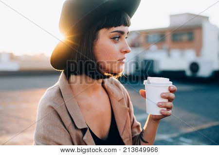 Natural beauty pretty woman with short haircut and in black fedora hipster hat sips on coffee or tea from blank white mockup take away to go cup on warm summer evening suring sunset in big city