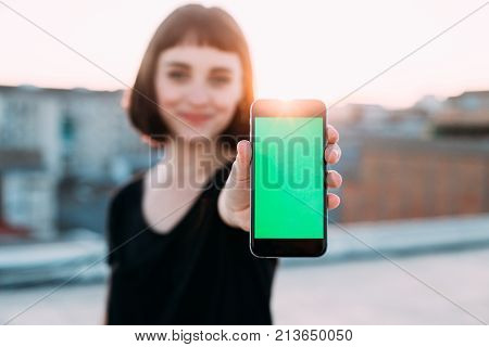 Beautiful young cute pretty woman smiles gently and shows smartphone with chroma key green screen to camera. Place for copy or screenshot of new application