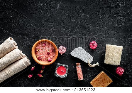 Romantic set for foot spa. Candles, salt, pumice stone, soap on black background top view.