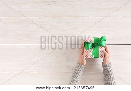 Gift wrapping background. Female hands holding handmade present box in dotted paper against white wooden table background. Bithday or christmas preparation concept, top view, copy space