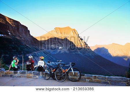 GLACIER NATIONAL PARK, MONTANA, USA - July 22, 2107: Three cyclists enjoy a beer together after a long ride to the top of Logan Pass in Glacier National Park