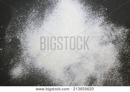 An overhead photo of wheat white flour sprinkled on the black wooden table. Top view place for text. Flour ready to knead the dough for baking bread cake or cupcake