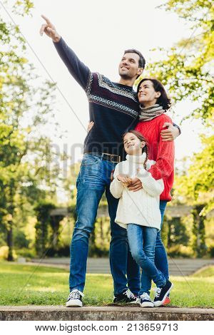 Vertical portrait of family of three members stand close to each other, embrace, have walk across autumn park, notice squirrels on tree. Friendly father, mother and daughter have good relationship