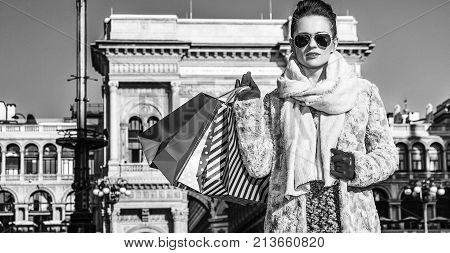 Rediscovering things everybody love in Milan. Full length portrait of modern traveller woman in fur coat and sunglasses in Milan Italy standing
