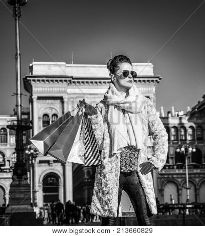 Rediscovering things everybody love in Milan. Full length portrait of trendy tourist woman in fur coat and sunglasses in Milan Italy looking into the distance