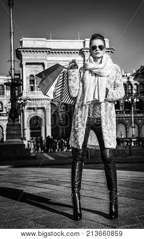 Rediscovering things everybody love in Milan. Full length portrait of elegant tourist woman with shopping bags in Milan Italy standing