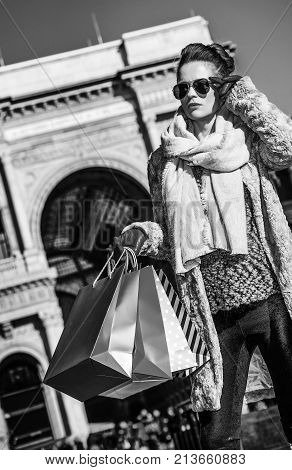 Rediscovering things everybody love in Milan. elegant woman in fur coat and sunglasses near Galleria Vittorio Emanuele II in Milan Italy looking into the distance