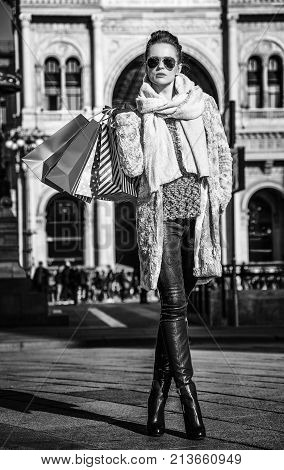 Rediscovering things everybody love in Milan. Full length portrait of trendy tourist woman with shopping bags near Galleria Vittorio Emanuele II in Milan Italy looking into the distance
