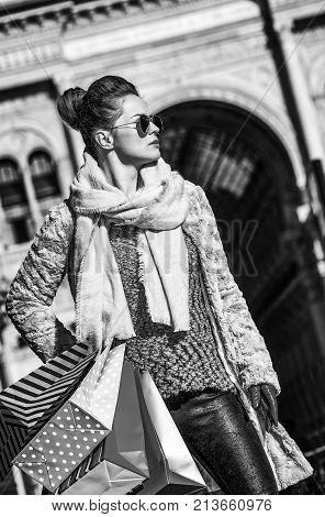 Rediscovering things everybody love in Milan. trendy tourist woman in fur coat and sunglasses at Piazza del Duomo in Milan Italy looking aside