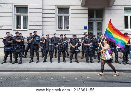 ZAGREB, CROATIA - JUNE 11, 2016: 15th Zagreb pride. LGBTIQ activist passing by police cordon holding rainbow flag.