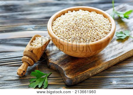 Pearl Barley In A Wooden Bowl And Scoop With Barley.