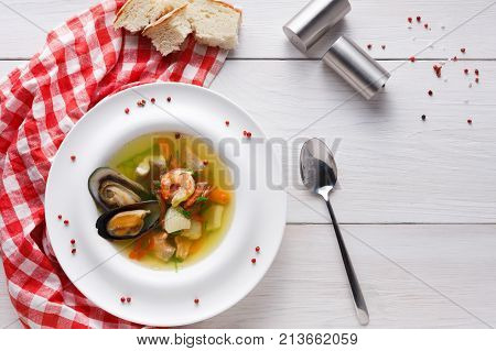 French cuisine restaurant. Seafood soup with white fish, shrimps and mussels in plate sprinkled with spices. Fresh exclusive meals on white wood with checkered cloth and cutlery, top view, copy space poster