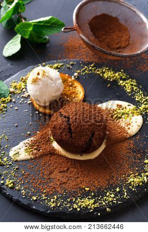 Exquisite french dessert. Chocolate fondant with creme anglaise and vanilla ice cream, sprinkled with cocoa, served on round slate finely decorated with orange citron and pistachio crumble, closeup