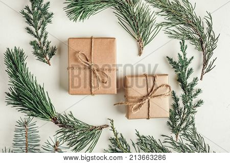 gift a surprise in the box is packed in brown vintage paper and tied with a rope scoop. Christmas concept. on a white homogeneous background. near a branch of a coniferous tree