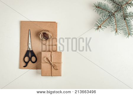 gift a surprise in the box is packed in brown vintage paper and tied with a rope scoop. Christmas concept. on a white homogeneous background. near a branch of a coniferous tree.near the scissors
