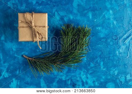 gift a surprise in the box is packed in brown vintage paper and tied with a rope scoop. Christmas concept. on a blue homogeneous background. near a branch of a coniferous tree