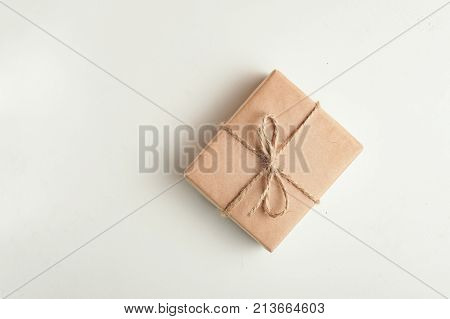 gift a surprise in the box is packed in brown vintage paper and tied with a rope scoop. Christmas concept. on a white homogeneous background