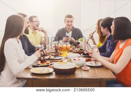 Friends meeting. Group of happy people drink wine at party dinner table in cafe, restaurant. Young company celebrate with alcohol and food at wooden table indoors.