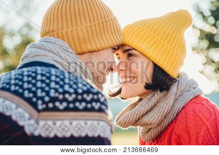 Adorable brunette female and her boyfriend stand closely to each other, look at eyes, smile happily as feel love and support. Good looking woman with scarf and hat has date with young attractive man