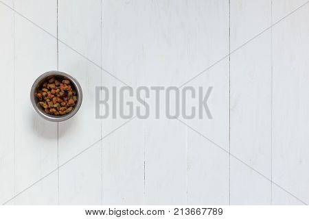 Dry pet food in bowl on white wooden background top view.