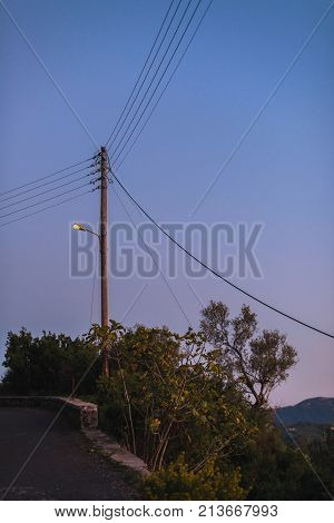 Old Telegraph Post With Illuminating Street Lantern At Sunset. Corfu, Greece.