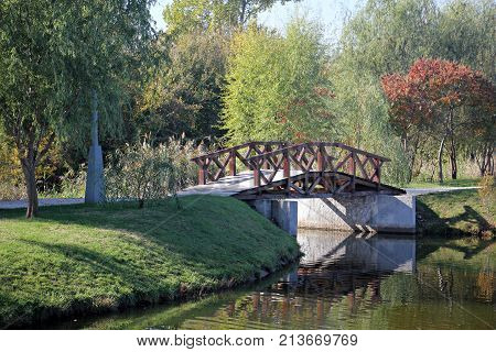 Wooden bridge in the park during fall season.