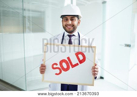 Happy young architect showing board with sold notice inside new building