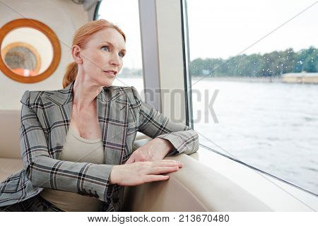 Mature businesswoman sitting by window of steamship and having a bit of rest