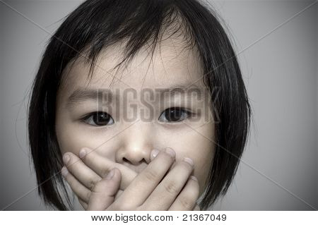 little girl covering her mouth, crime witness concept.
