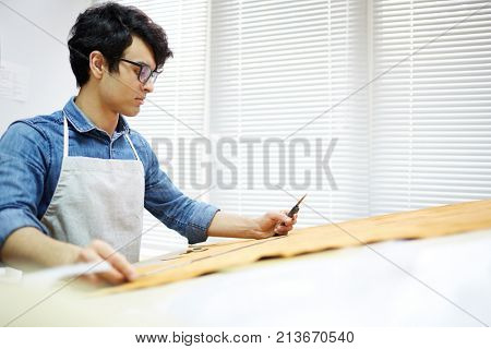 Self-employed cobbler measuring piece of leather for new pair of shoes