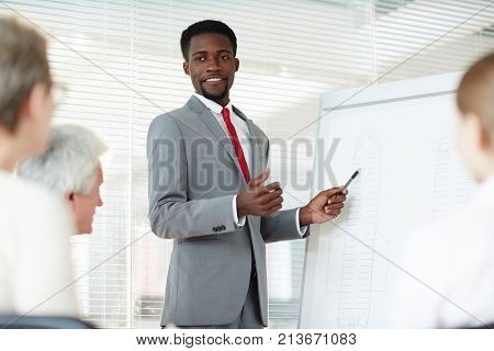 Young confident expert pointing at whiteboard during presentation of his ideas of accident