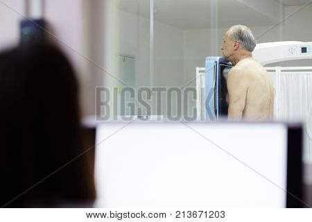 Shirtless senior man standing by screen of x-ray machine during examination of lungs and heart