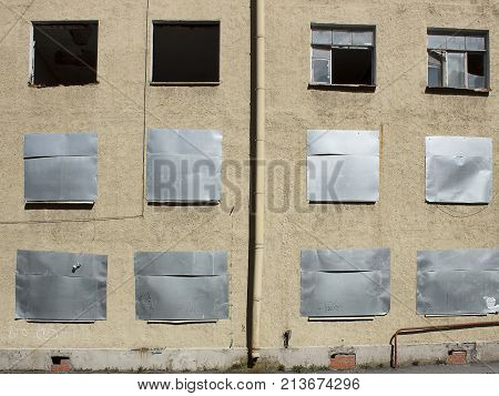 An abandoned house with metal- lad windows