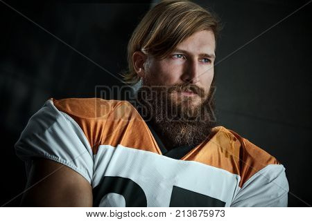 Portrait of bearded american football player looking away with dedication.