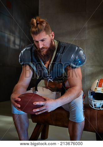 American football player in protective armor sitting on brench in locker room, holding ball and thinking.