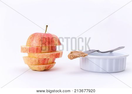 Apple in slices and peanut butter. An apple stacked in slices and a knife with peanut butter on a bowl.