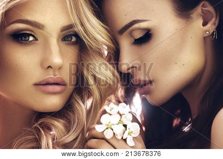Close up fashion portrait of amazing blonde and brunette woman, perfect skin, natural make up, pure beauty, couple, luxury, elegant. Outdoor spring blossom.