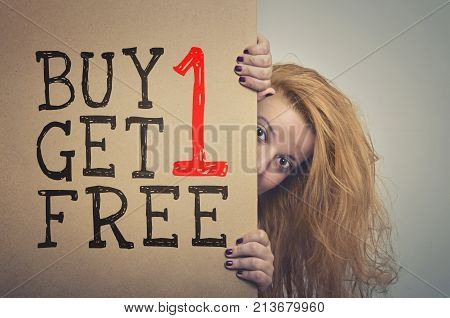 Woman with long hair peeking behind a Buy 1 Get 1 Free billboard poster.