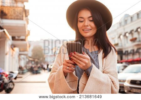 Stylish asian woman in black hat texting message on mobile phone while walking on the city street
