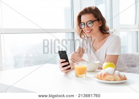 Photo of cheerful young amazing woman sitting indoors at the table with juice and croissant and corn flakes. Looking aside chatting by mobile phone.