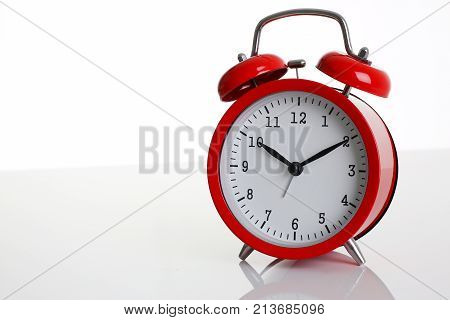 Red alarm clock isolated on white background shows ten hours ten minutes of the morning time to get up to wake up and have breakfast morning or evening jog to go to work.